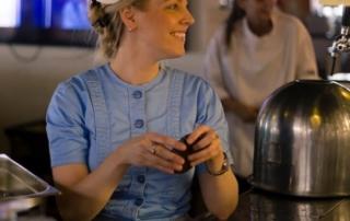 Sonja Gorter in klederdracht achter de bar Brasserie Palace